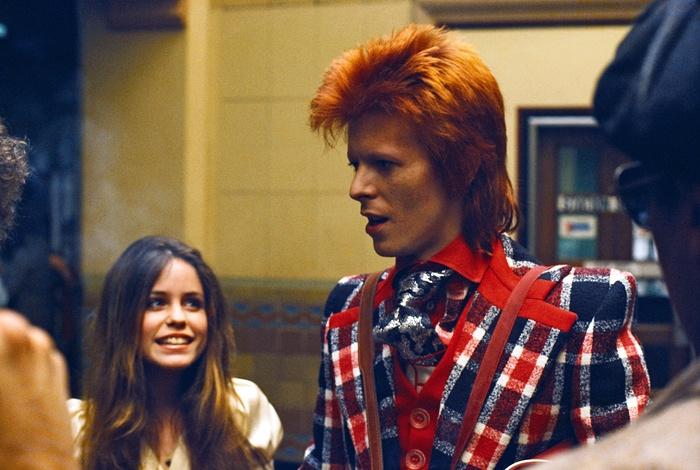 Esta é uma linda foto do David Bowie. A moça que olha para ele com admiração poderia ser eu, você ou qualquer um de nós que se sentiu tocado por ele ter o incrível de dom de, em sua estranheza, nos tornar familiares Crédito da foto: Michael Ochs-Corbis